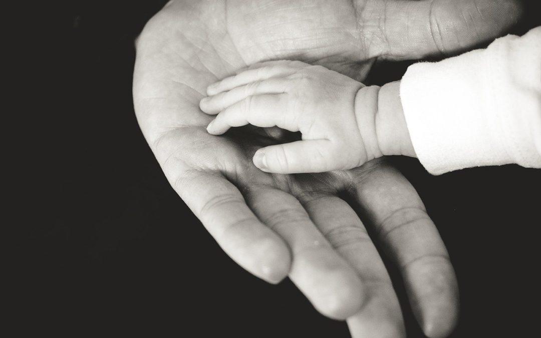 Main de bébé dans un main adulte